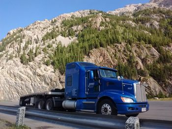 Blue Kenworth flatbed parked in front of a mountain