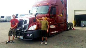 An instructor and his trainee in front of their tractor trailer at Prime Inc headquarters