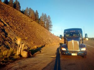 Blue Kenworth tractor trailer parked on the side of the road at sunset