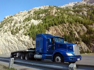 Blue Kenworth tractor trailer parked in front of a mountain