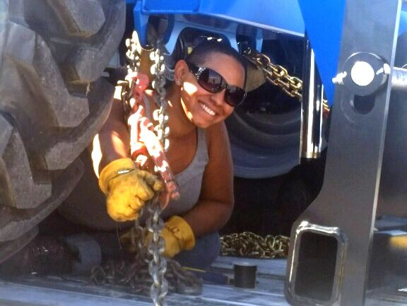 Female flatbed driver securing a load with chains