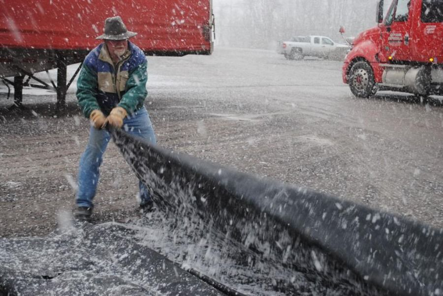 flatbed truck driver folding up his tarp in the winter