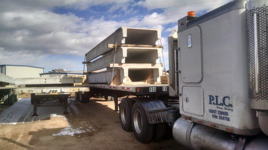 flatbed trailer loaded with cement bridge pieces
