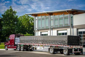 Maverick Transportation flatbed truck at a terminal